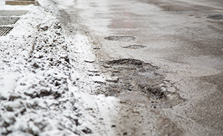 Potholes are the result of drury winter conditions and affect people driving throughout Chicago. On the corner of State and Harrison.