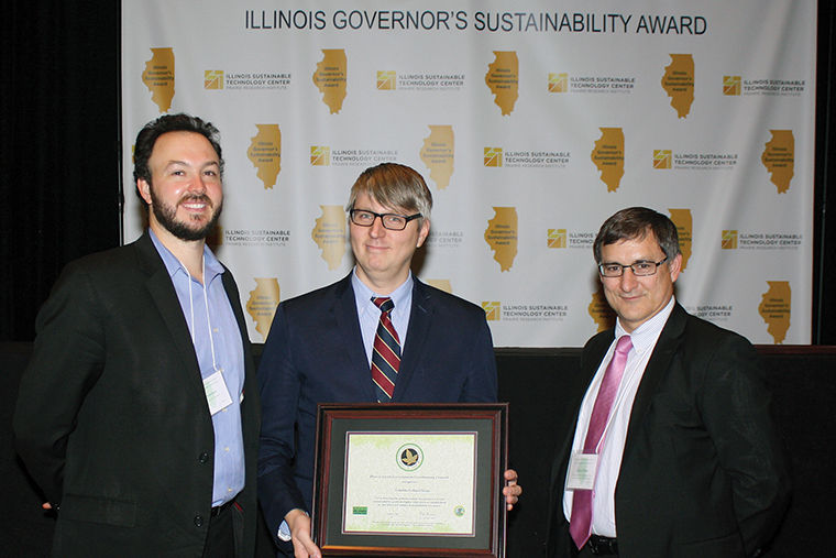 John Wawrzaszek (center) accepted the Gold Level Campus Sustainability Compact Award based on the various environmental efforts the college has initiated on campus.