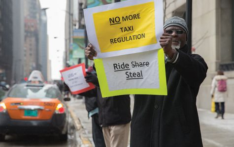 Chicago taxi driver Rocky Mmoma protests ridesharing apps, such as Uber, outside City Hall on Feb. 17 as other drivers circled the building from 6–10 a.m.