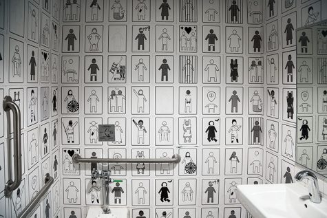 """""""Genderpoo"""" covers the walls of the bathroom on the fifth floor of the 33 E. Congress Parkway Building to evoke conversation about gender-inclusivity."""