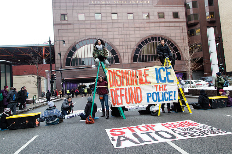 Pro-immigrant rights activists blocked a major Loop intersection, demanding Immigration and Customs Enforcement (ICE) cease raids and deportations in the U.S.