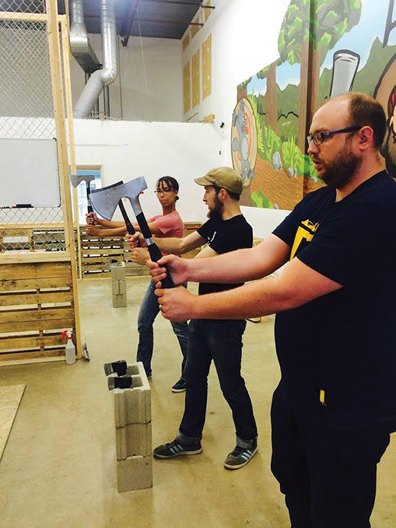 Participants at Bad Axe Throwing in Winnipeg, Manitoba, learn how to throw axes  with help from the axe throwing coach, which acts as the host of the party group.