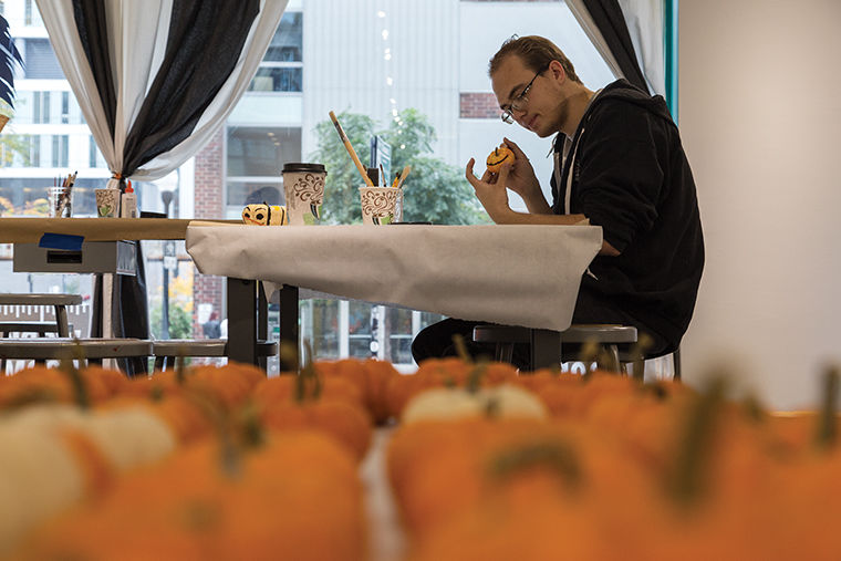 Freshman cinema art + science major Micahel Witek paints a pumpkin Oct. 21 at an event in the 623 S. Wabash Ave. Building as part ofthe annual WAC Art Crawl celebration.