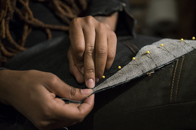 Fashion designer Sheila Rashid sews a pair of overalls, for which she has become famous for at her studio on Feb. 23.