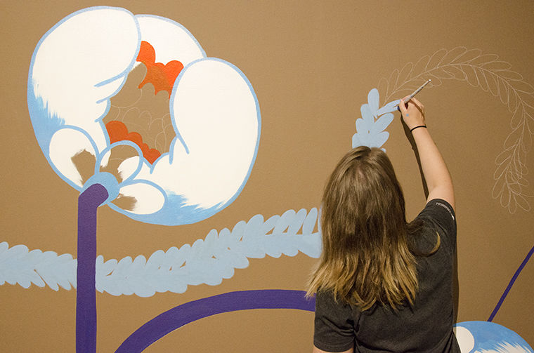 Student worker Lauren VanReken recreates a mural by Gloria Talamantes as part of the exhibition in the back room of the Glass Curtain Gallery, 1104 S. Wabash Ave.