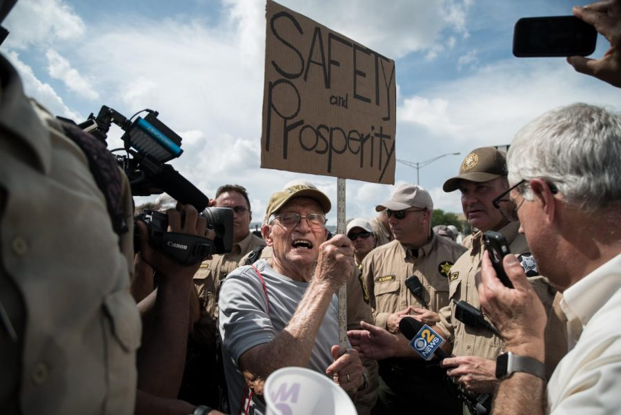 A protestor hands his sign over as police arrest him on the entrance ramp for Kennedy Expressway, near O'Hare International Airport on Labor Day, Sept. 3.