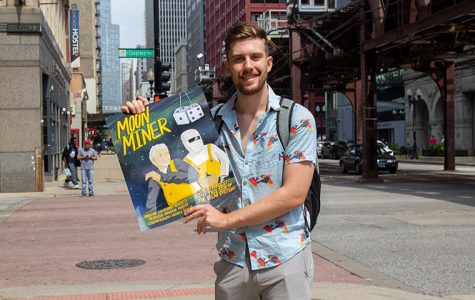 Senior Christopher Rohrbeck, Cinema Arts and Science Major, holding the poster of film