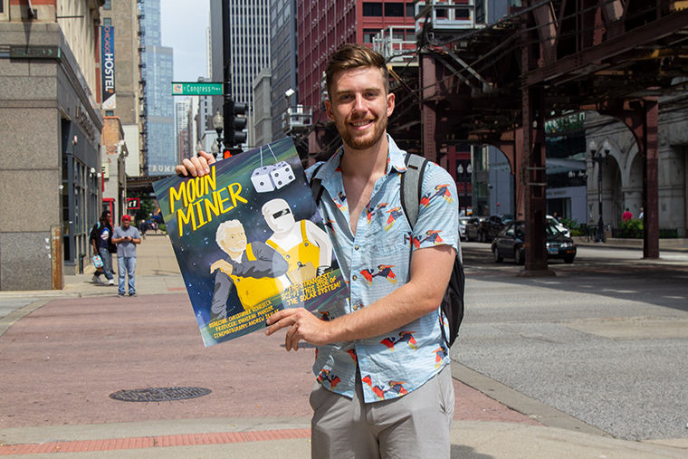 Senior Christopher Rohrbeck, Cinema Arts and Science Major, holding the poster of film Moon Miner that he directed and wrote.