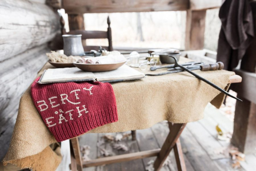 A Liberty or Death scarf hangs over the edge of a table displaying the tools of a Revolutionary War surgeon.