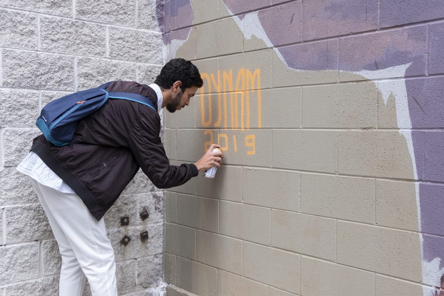 Moroccan artist Youness Amriss, who also goes by the artist name DYNAM, creates a mural for the Wabash Arts Corridor.