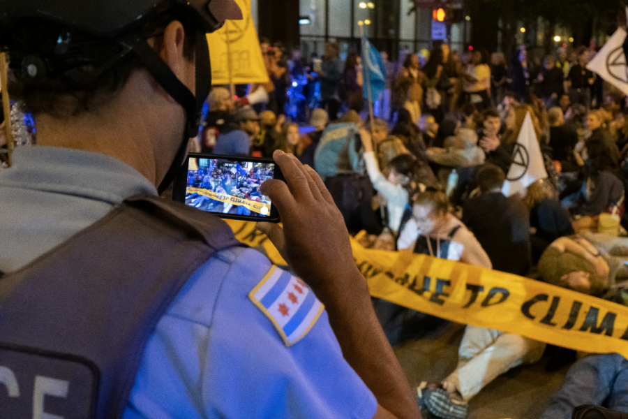 A police officer records Extinction Rebellion Chicago's Declare Climate Emergency march in front of Daley Plaza on Oct. 7.