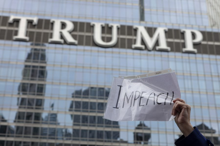 A protester holds up a sign that reads,