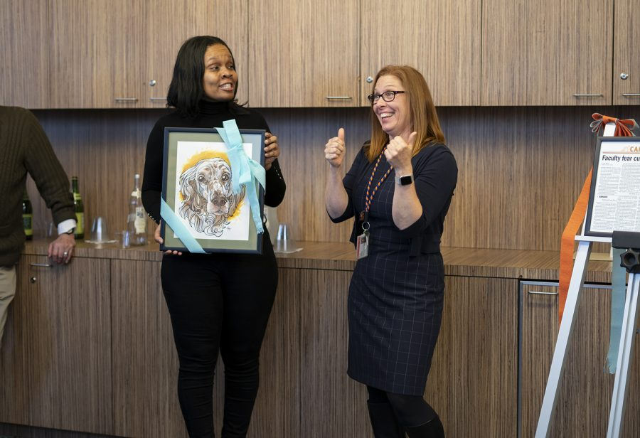 Marvery Griffin, director of finance and budget analysis, presents a surprise gift for Senior Associate Provost Suzanne Blum Malley. The painting, made by a Columbia student, pictures one of Blum Malley's dogs.