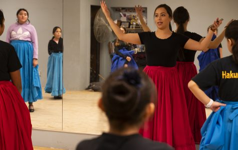 Artistic Director Blanca Acevedo walks junior dancers, dressed in blue and red practice skirts, through a choreography step for a dance originating in the Jalisco region of Mexico.