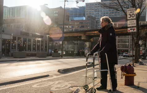 Con Buckley, part-time faculty member in the Humanities, History and Social Sciences Department, stands with her leg brace and walker near the concrete-protected bike lane that she tripped over, shattering her patella.