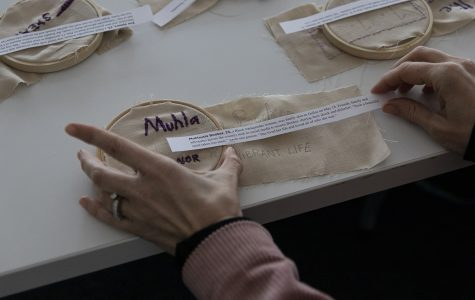 Colbey Reid, chair of the Fashion Studies Department, and other attendees are given the name and age of a transgender woman of color by quilter Melissa Blount to learn more about the circumstances in which they were killed, and to embroider their names and ages into the fabric for Blount's quilt.