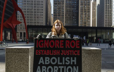 Moriah Stefanski, 19, an anti-abortion activist, protests across the street from the Planned Parenthood Illinois Action Rally on Wednesday.