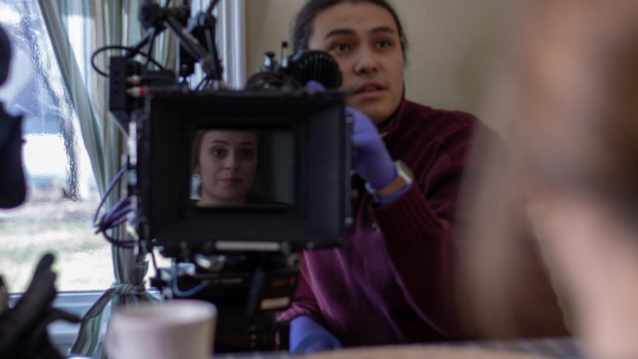 Students Lucas Miroslaw (right) and Giana Carli (center) work on the film set of a