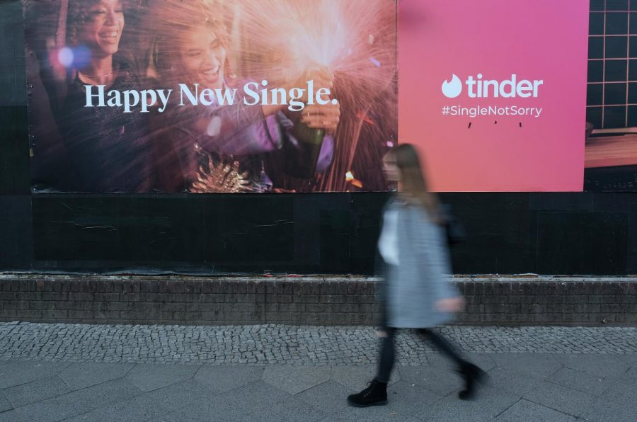 A young woman walks past a billboard advertisement for the dating app Tinder in Berlin, Germany. (Photo by Sean Gallup/Getty Images)