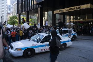 A group of protesters destroy a police vehicle, slashing its tires and jumping on the dash to shatter the glass.