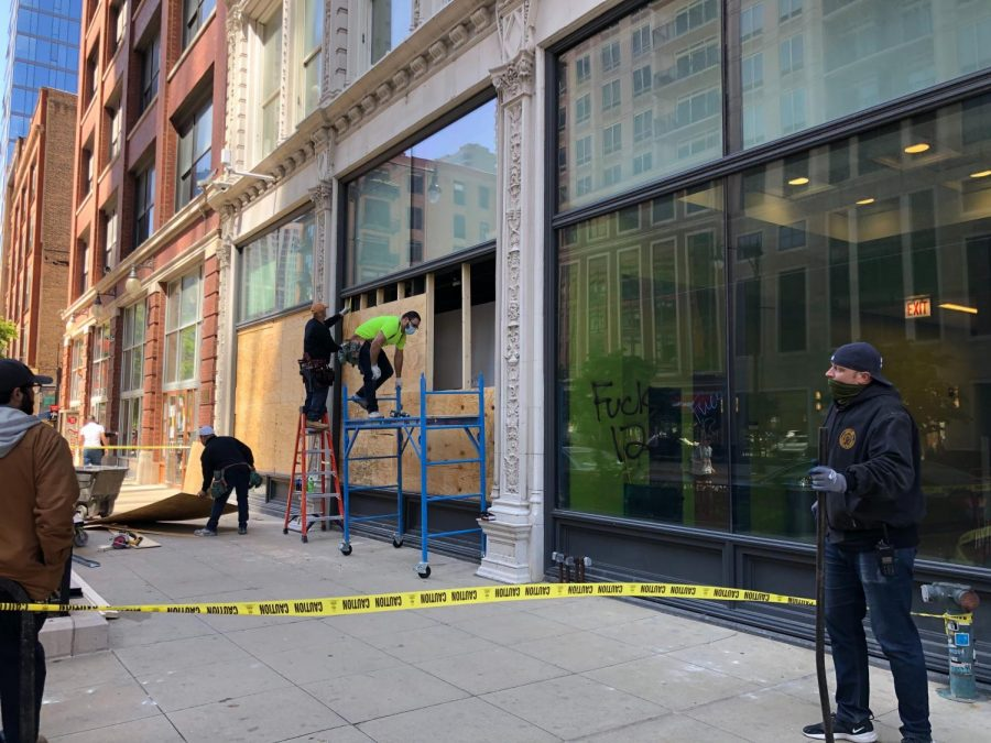 At the 1104 S. Wabash Ave. building, workers repair shattered windows and wash away graffiti.