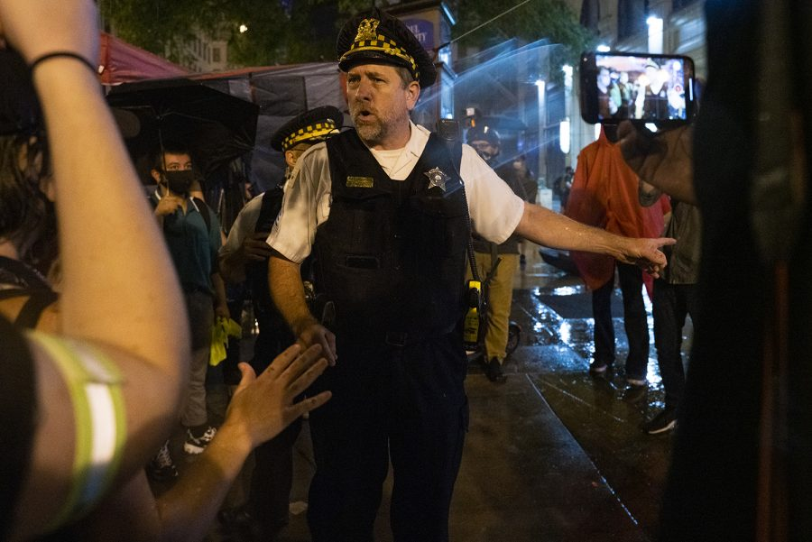 An officer issues a warning to protesters, threatening to bring officers closer to protesters if vandalism to nearby buildings occurs.