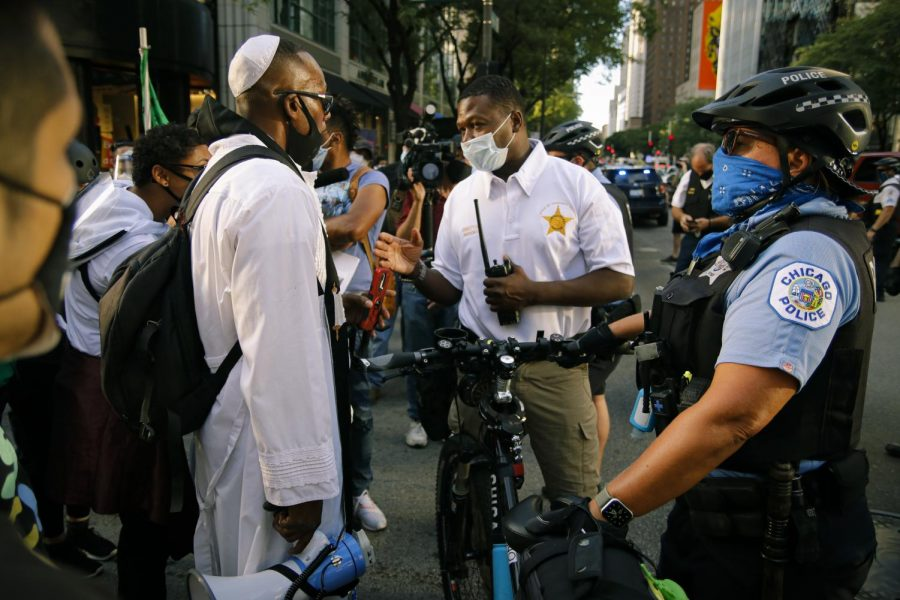 Yosef negotiates with CPD Director of Public Engagement Glen Brooks to allow protesters at the corner of East Ohio Street and North Michigan Avenue into the street.