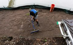 Bill Wei, consultant at Accenture, sweeps LECA, a lightweight soil made of clay pebbles, around the platform, covering the wetter areas with excess soil.