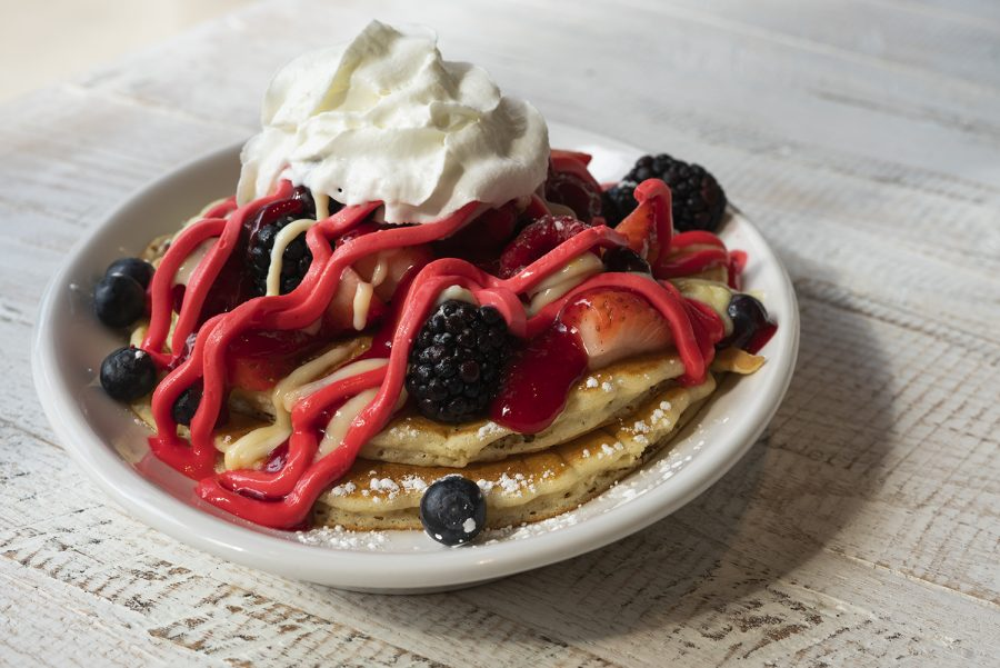 The Signature Honeyberry pancakes are topped with colorful berry mascarpone filling, fresh berries, vanilla crème angles over a spread of blackberry coulis.