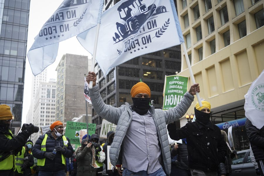 """Banners made using PVC pipes that read """"No Farmers, No Food"""" wave over solidarity marchers in Daley Plaza."""