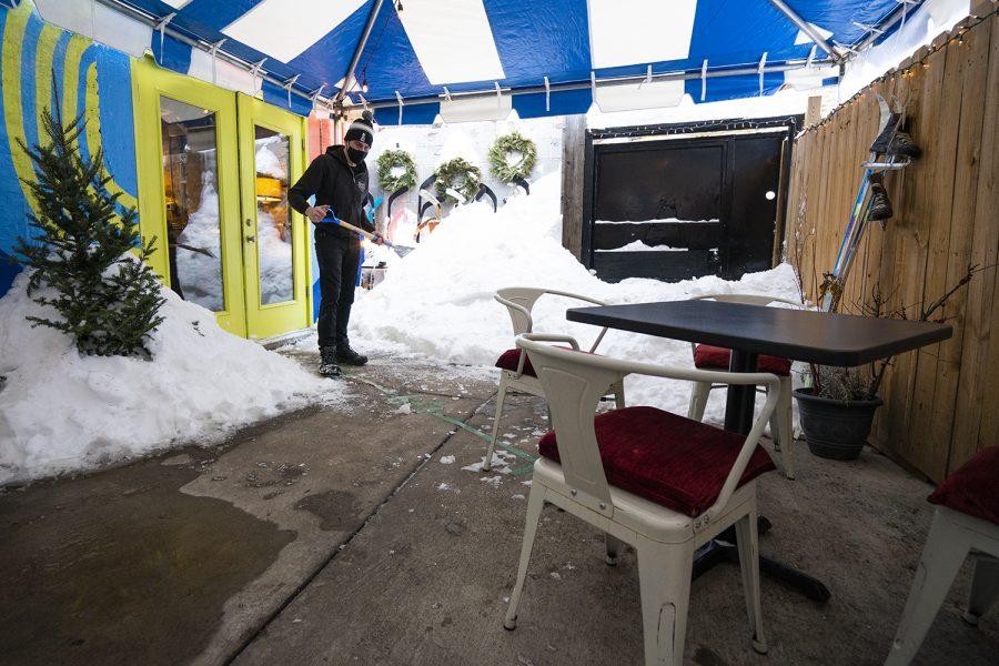 """Andrew Barbera, co-owner of Beard and Belly, 6155 N. Broadway, clears ice off the ground in the restaurant's outdoor seating area. The business uses heated lamps to make outdoor dining during the winter more accessible, but the owners have avoided erecting any sealed structures. """"We've tried to do everything very cautiously,"""" Barbera said. """"We just didn't feel like it was appropriate to build an indoor space outdoors."""""""