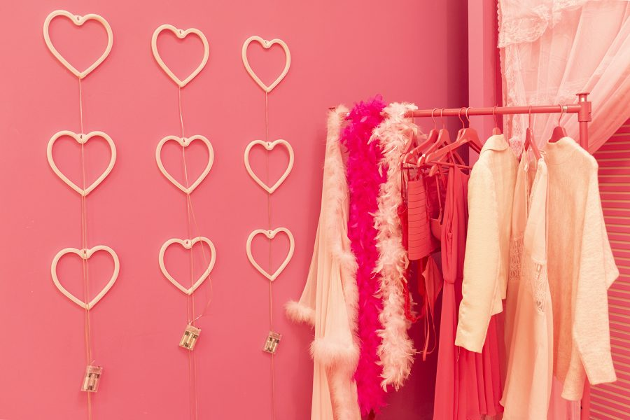 """Boas and dresses hang in Magic Selfies' """"Barbie Land"""" room next to hearts that illuminate the room with neon pink."""