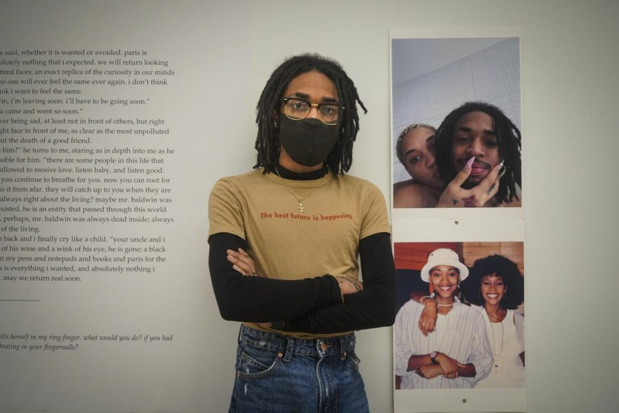 Isaiah Moore, a peer mentor with Student Diversity and Inclusion, stands in front of a photo of themselves that is a part of the exhibit