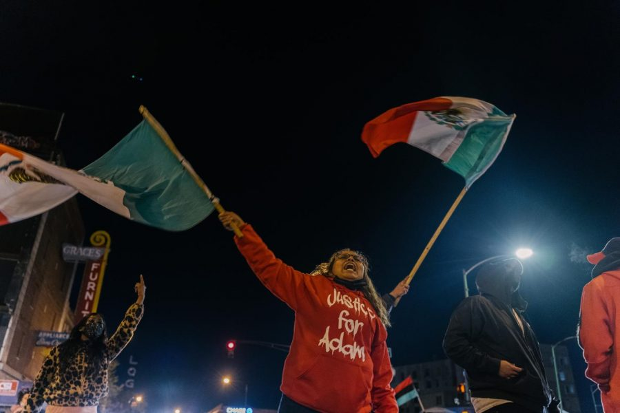 """A woman waves a Mexican flag wearing a """"Justice for Adam"""" hoodie."""