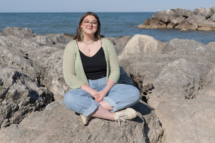 Abby McFarland sits on rocks in front of Lake Michigan.