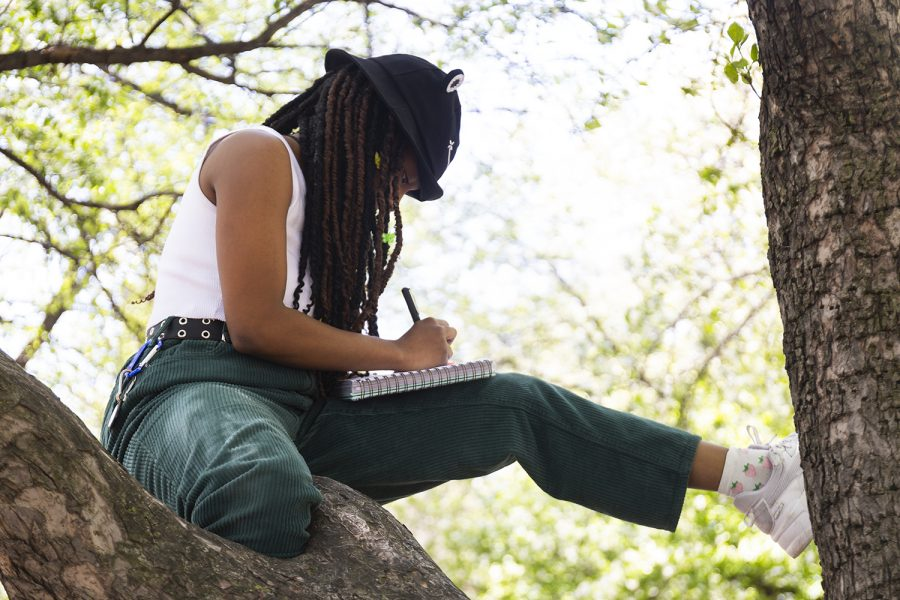 Samira Carr, a sophomore musical theatre major who learned about the event through her friend Charlotte Briskin, sits in a tree and doodles.