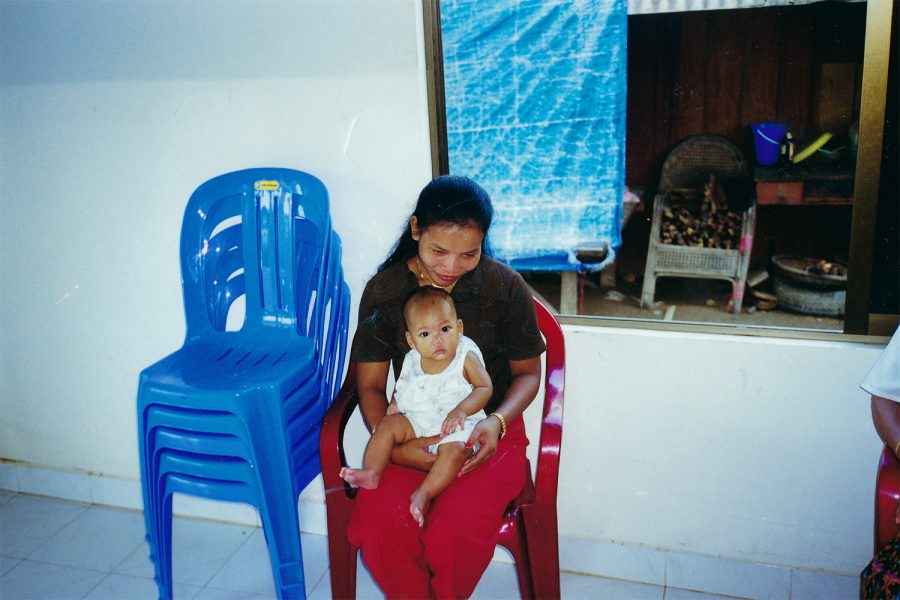 Elizabeth Jacobs sits on her nannys lap before she was adopted from an orphanage in Cambodia. Courtesy of