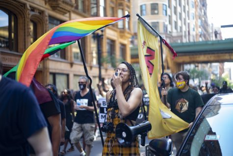 A demonstrator marches with Pride and Juneteenth flags on Dearborn Avenue during the 2021 March for Us rally.