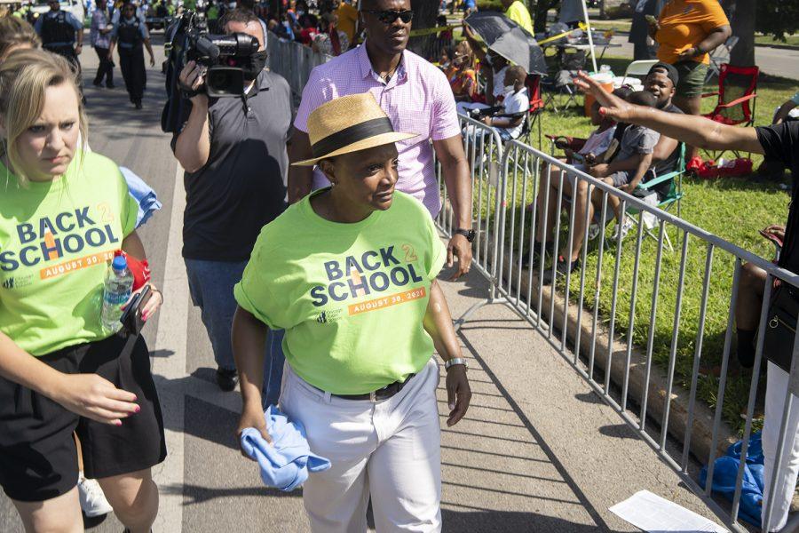 Mayor Lori Lightfoot walks alongside Chicago Public Schools representatives handing out T-shirts that say