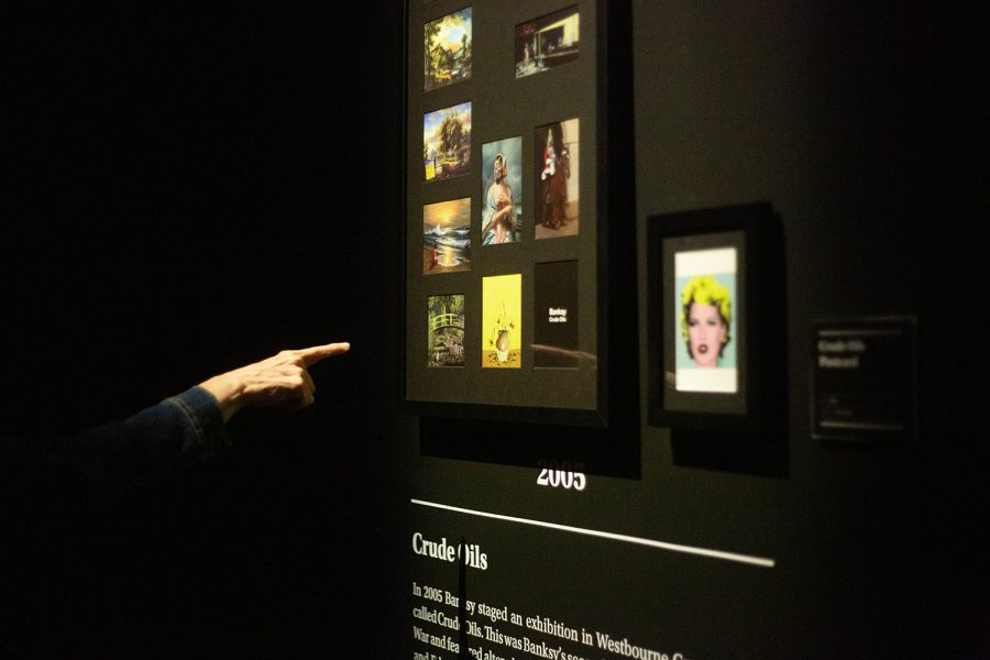 """A patron marvels at photographs of Banksy's 2005 exhibition """"Crude Oils,"""" a series of the anonymous artist's dark reimaginings of classic works of art."""