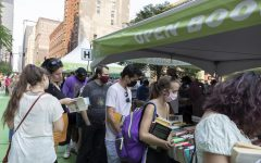 Lit Fest attendees gather around a booth looking for a new read.