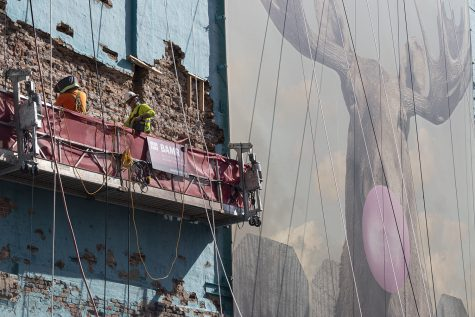Construction crews re-point the southern brick wall of the 33 E. Ida B. Wells Drive building next to the iconic Moose Bubblegum Bubble banner on Tuesday, Aug. 24.