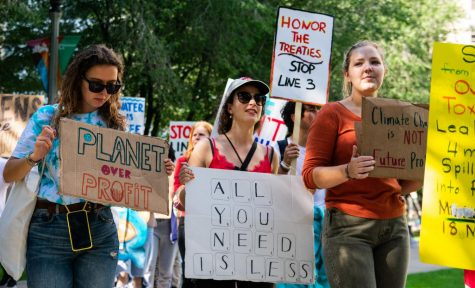 Protesters holding decorated signs listen to the speakers demanding action on climate change.