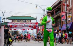 A man dressed as popular Super Mario character Yoshi runs through Chinatown, one of the most popular marathon spots.